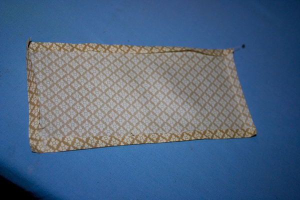 a yellow gold rectangular piece of fabric with all four sides folded and ironed sits on a light blue background.