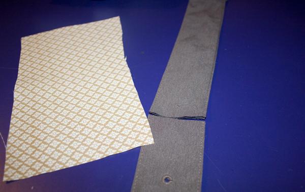 a yellow gold rectangular piece of fabric sits near a gray green belt that has been cut.