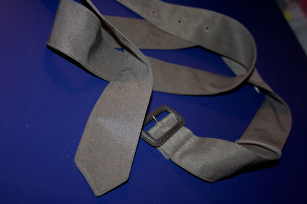 a gray green belt sits slightly curled up on a bright blue background.