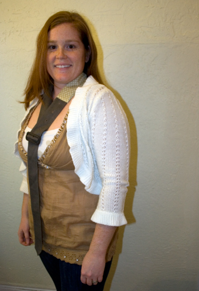 woman stand in front of a yellow wall wearing a golden brown tank top and a white knit cardigan.  She is wearing an upcycled belt necklace.