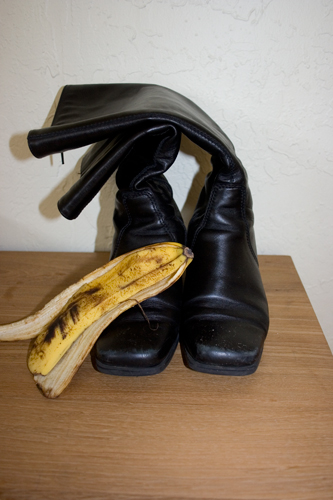 black leather boots a banana peel and a wood table
