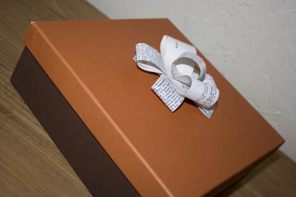 paper bow sitting on a brown box with an orange top
