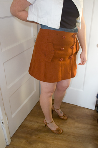 model wearing an orange wool skirt, navy blue tank and white short sleeve jacket standing on a wood floor and against a white background