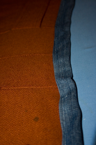 close up of denim and orange fabric sewn together