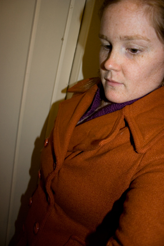 close up of a woman wearing an orange wool jacket standing in front of a white background
