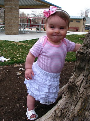 a baby girl wears a white ruffle skirt