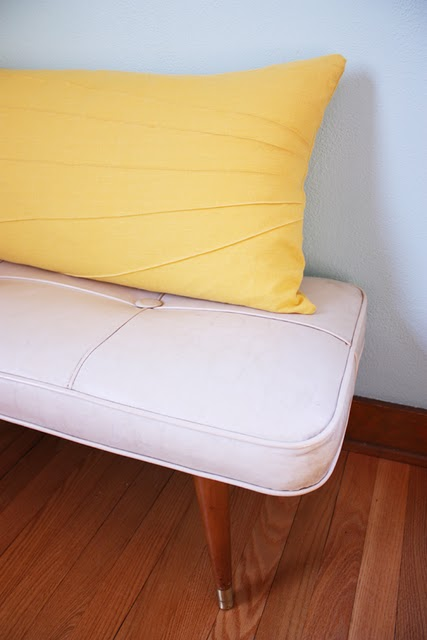 a yellow long pillow sits on top of a white cushioned bench