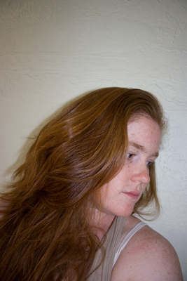 photograph of a redheaded woman from the side. She has long wavy hair.