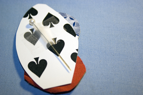 the backside of a playing card boutonierre with a pin taped to it