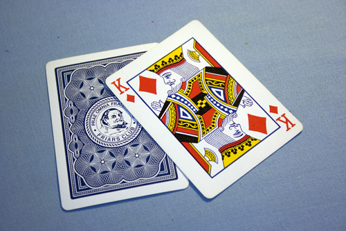 the kings of diamonds and another face down card on a light blue background