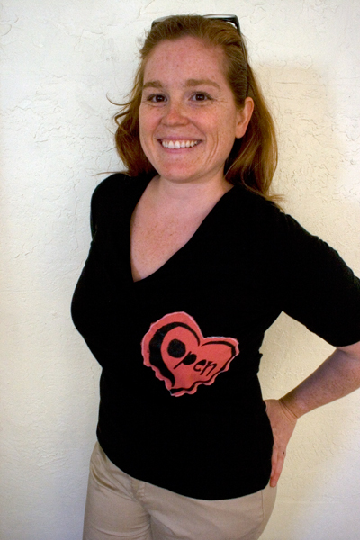 a woman wears a black shirt with a red heart with the words open heart on the right hand side printed on to the shirt