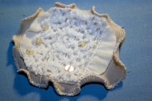 a beaded cream circled piece of fabric sits inside a circled piece of khaki fabric