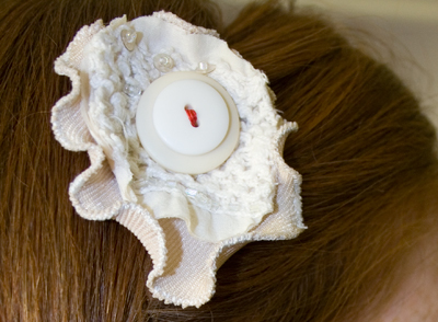 close up of a cream and khaki fabric flower hairpin