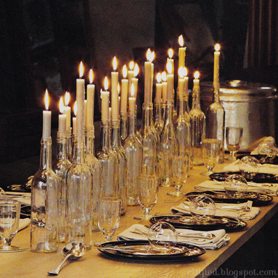 clear glass wine bottles hold candles and light a table