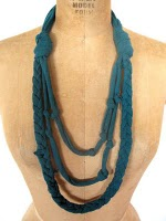 teal layered necklace made from a tshirt sits on a dress form
