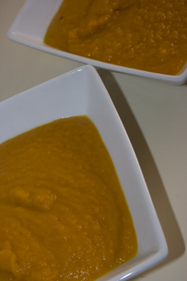 to white bowls filled with carrot curry soup