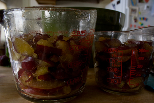 chopped plums placed in a measuring cup