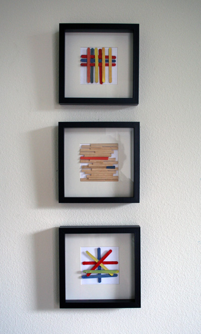 three framed works of popsicle stick art hang on a white wall