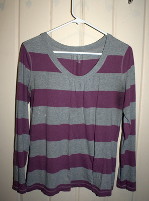 a purple and grey horizontally striped long sleeved shirt hangs on a white hanger