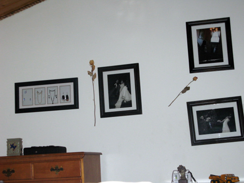 a white wall is decorated with a jewelry holder and three wedding photographs
