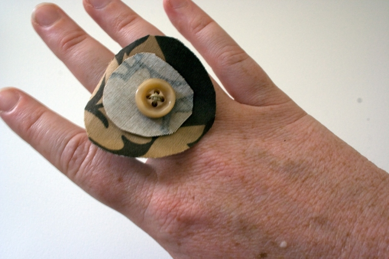 a large fabric ring sits on the middle finger of a woman's hand.  The ring has a large brown circle with a white circle centered on top of it and a small tan button on the middle of that.