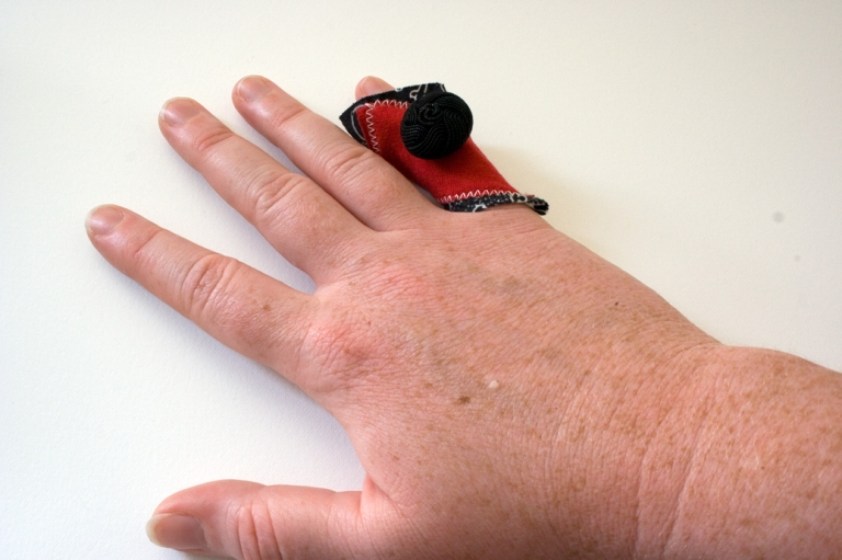 the right hand of a woman is place on a white background a fabric ring of red and black sits on the pinky finger