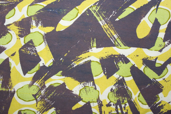 purple screenprint on a green and yellow fabric