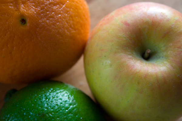 close up of an apple, orange and a lime